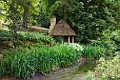 ASTHALL MANOR  OXFORDSHIRE: HERMITAGE BY THE POND BUILT OF AOK POSTS AND THATCH BY ISABEL BANNERMAN