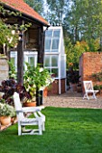 ULTING WICK  ESSEX - THE GARDEN IN AUTUMN - VIEW TO GREENHOUSE WITH WHITE SEAT  CONTAINERS PLANTED WITH AEONIUM SCHWARZKOPF AND BRUGMANSIA