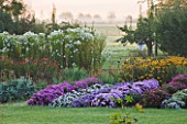WATERPERRY GARDENS  OXFORDSHIRE: THE TRIAL BEDS AT DAWN WITH VIEW TO FIELDS BEYOND