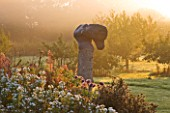WATERPERRY GARDENS  OXFORDSHIRE: THE TRIAL BEDS AT DAWN WITH SCULPTURE EMERGING FROM MIST