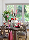 JACKY HOBBS HOUSE  LONDON: AUTUMN TABLE SETTING WITH MIXTURE OF BRIGHT SEASONAL DAHLIAS DRESSING THE TABLE WITH COLOURED CANDLES AND NAPKINS