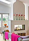 JACKY HOBBS HOUSE  LONDON: THE LIVING ROOM WITH PINK AND GREY THROWS OVER SOFA  FIRE WITH DAHLIAS IN GLASS BOTTLES ON MANTELPIECE