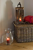 JACKY HOBBS HOUSE  LONDON: WICKER BASKET RED THROW AND WOODEN AND GLASS STROM LANTERNS WITH CANDLES