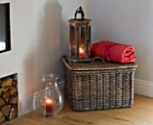 JACKY HOBBS HOUSE  LONDON: FIRESIDE SCENE WITH LOG PILE  WICKER BASKET RED THROW AND WOODEN AND GLASS STROM LANTERNS WITH CANDLES