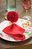 JACKY HOBBS HOUSE  LONDON: TABLE SETTING WITH FLORAL PLATE  RED NAPKIN AND RED DAHLIA FENSTERGUCKER