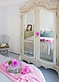 JACKY HOBBS HOUSE  LONDON: PINK DAHLIAS DECORATE THE PALE GREY FRENCH STYLE BEDROOM WITH MIRROR FRONTED WARDROBE