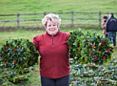 HOLLY AND MISTLETOE AUCTION  TENBURY WELLS  WORCESTERSHIRE - LADY WITH HOLLY WREATHS ON ARMS