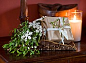 BASKET ON TABLE IN DINING ROOM WITH WRAPPED PRESENT AND MISTLETOE : STYLING BY JACKY HOBBS
