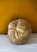 CHATEAU DU RIVAU  LOIRE VALLEY  FRANCE: PUMPKIN BESIDE PILLOW IN THE BRIDAL ROOM BEDROOM IN THE ROYAL STABLES