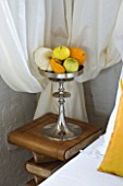 CHATEAU DU RIVAU  LOIRE VALLEY  FRANCE: THE BRIDAL ROOM BEDROOM WITH GOURDS AND PUMPKINS IN A METAL CONTAINER ON BOOK BEDSIDE TABLE IN THE ROYAL STABLES