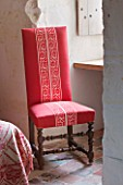 CHATEAU DU RIVAU  LOIRE VALLEY  FRANCE: RED THEMED BEDROOM - RED CHAIR BY WINDOW