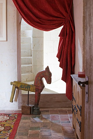 CHATEAU_DU_RIVAU__LOIRE_VALLEY__FRANCE_RED_THEMED_BEDROOM__WOODEN_HORSE_BY_STAIRCASE