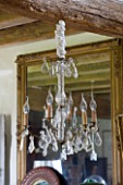 ROQUELIN  LOIRE VALLEY  FRANCE: DINING ROOM; DECORATIVE GLASS CHANDELIER IN FRONT OF VINTAGE GILT GLASS MIRROR