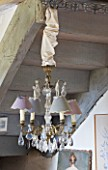 ROQUELIN  LOIRE VALLEY  FRANCE: SITTING ROOM; PASTEL SHADED DECORATIVE GLASS CHANDELIER BENEATH THE STAIRCASE