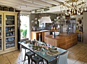 ROQUELIN  LOIRE VALLEY  FRANCE: KITCHEN; ZINC TOP DINING TABLE WITH PAINTED WOODEN CHINA CABINET  MAIN KITCHEN ISLAND IS AN OLD SHOP COUNTER  WOODEN BEAMED CEILINGS AND FLAG FLOOR