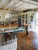 ROQUELIN  LOIRE VALLEY  FRANCE: KITCHEN; VINTAGE SHOP COUNTER AS MAIN ISLAND UNIT  HANGING KNIFE AND FORK RACK  ZINC TOP TABLE AND BUTCHERS BLOCK DRESSER