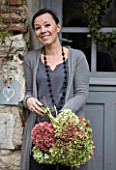 ROQUELIN  LOIRE VALLEY  FRANCE: OWNER ALINE CHASSINE WITH HYDRANGEAS OUTSIDE THE FRONT DOOR OF THE FARMHOUSE