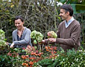 ROQUELIN  LOIRE VALLEY  FRANCE: OWNERS ALINE AND STEPHANE CHASSINE OUTSIDE THEIR RENOVATED FARMHOUSE CUTTING HYDRANGEA HEADS FOR INSIDE THE HOUSE