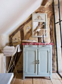 ROQUELIN  LOIRE VALLEY  FRANCE: BATHROOM; A SMALL BATHROOM FITS UNDER THE ROOF EAVES WITH PAINTED WOODEN CUPBOARD AND METAL TOWEL HOLDER