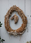 ROQUELIN  LOIRE VALLEY  FRANCE: OUTHOUSE DOOR; A SIMPLE TWIG AND CONE CHRISTMAS WREATH