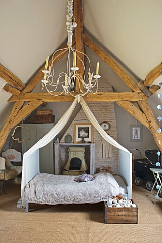 ROQUELIN__LOIRE_VALLEY__FRANCE_CHILDS_ROOM_EAVED_AND_BEAMED_BEDROOM_WITH_CENTRAL_CANOPIED_METAL_FRAM