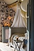 ROQUELIN  LOIRE VALLEY  FRANCE: BEDROOM; PAINTED WOODEN FRENCH BED DRESSED IN VINTAGE TOILLE DE JOUEY PRINTED QUILT. BEAMED CEILING AND PRINTED BLACK AND WHITE FACES WALLPAPER