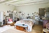 ROQUELIN  LOIRE VALLEY  FRANCE: MASTER BEDROOM; WITH PALE WOODEN CEILING BEAMS AND WOODEN FLOOR  WALLS DECORATED WITH PERSONAL ARTEFACTS  MEMENTOES AND PHOTOGRAPHS