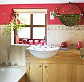 RICKYARD BARN HOUSE  OXFORDSHIRE: DESIGNERS JANE AND CLIVE NICHOLS. BATHROOM WITH TILES AND SINK  RED/PINKWALLS  MISTLETOE ON MIRROR - CHRISTMAS