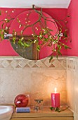 RICKYARD BARN HOUSE  OXFORDSHIRE: DESIGNERS JANE AND CLIVE NICHOLS. BATHROOM WITH TILES  PINK/ RED PAINTED WALL  SINK  CANDLE AND MISTLETOE AROUND CIRCULAR MIRROR - CHRISTMAS