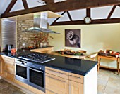 RICKYARD BARN HOUSE  OXFORDSHIRE: DESIGNERS JANE AND CLIVE NICHOLS. KITCHEN WITH SEPIA TONE PHOTO CANVAS BY CLIVE NICHOLS ON KITCHEN WALL WITH DRIED FRUIT DISPLAY ON TABLE