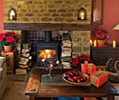 RICKYARD BARN HOUSE  OXFORDSHIRE: DESIGNERS JANE AND CLIVE NICHOLS. LIVING ROOM AT CHRISTMAS WITH WRAPPED PRESENTS  POINSETTIAS IN CONTAINERS AND WOOD BURNING FIRE