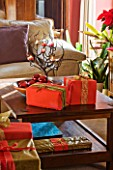RICKYARD BARN HOUSE  OXFORDSHIRE: DESIGNERS JANE AND CLIVE NICHOLS. LIVING ROOM AT CHRISTMAS WITH WRAPPED PRESENTS ON COFFEE TABLE