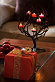 RICKYARD BARN HOUSE  OXFORDSHIRE: DESIGNERS JANE AND CLIVE NICHOLS. LIVING ROOM AT CHRISTMAS WITH WRAPPED PRESENTS  DARK RED BAUBLES IN A WOODEN BOWL AND CANDLE HOLDER
