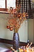 RICKYARD BARN HOUSE  OXFORDSHIRE: DESIGNERS JANE AND CLIVE NICHOLS: CHRISTMAS DECORATION - CONTAINER WITH BERRIES  TWIGS AND BAUBLES