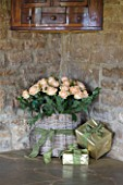 RICKYARD BARN HOUSE  OXFORDSHIRE: DESIGNERS JANE AND CLIVE NICHOLS. LIVING ROOM - WRAPPED PRESENTS AND BASKET FILLED WITH ROSES