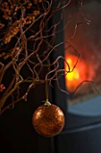 RICKYARD BARN HOUSE  OXFORDSHIRE: DESIGNERS JANE AND CLIVE NICHOLS. TWIGS AND BAUBLE IN FRONT OF FIRE AT CHRISTMAS