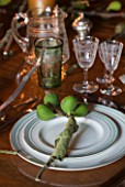 RICKYARD BARN HOUSE  OXFORDSHIRE: DESIGNERS JANE AND CLIVE NICHOLS. CHRISTMAS DECORATION ON DINING TABLE WITH FIG BRANCH CUT FROM THE GARDEN USED AS A NAPKIN HOLDER