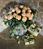 RICKYARD BARN HOUSE  OXFORDSHIRE: DESIGNERS JANE AND CLIVE NICHOLS. WRAPPED PRESENTS AND BASKET WITH ROSES IN THE LIVING ROOM