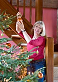 RICKYARD BARN  OXFORDSHIRE: CHRISTMAS - JANE NICHOLS ATTACHING BAUBLE TO THE CHRISTMAS TREE