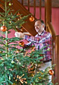 RICKYARD BARN  OXFORDSHIRE: CHRISTMAS - CLIVE NICHOLS ATTACHING BAUBLE TO THE CHRISTMAS TREE