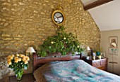 RICKYARD BARN  OXFORDSHIRE: CHRISTMAS - BEDROOM - GOLD LEAF EAGLE MIRROR ABOVE BED  BLUE BED SPREAD AND IVY DECORATED HEADBOARD