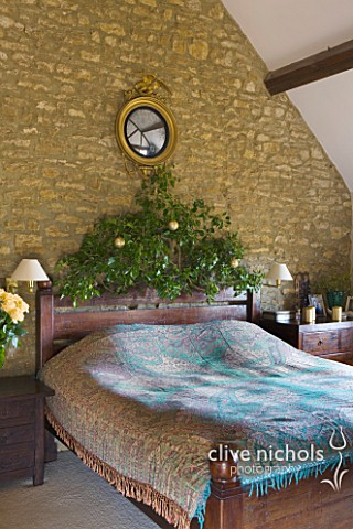 RICKYARD_BARN__OXFORDSHIRE_CHRISTMAS__BEDROOM__GOLD_LEAF_EAGLE_MIRROR_ABOVE_BED__BLUE_BED_SPREAD_AND