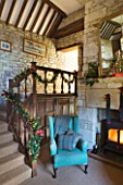 FULBROOK HOUSE: GALLERIED MAIN HALL WITH COTSWOLD STONE FIREPLACE  LOG BURNING STOVE AND LEATHER AND UPHOLSTERED ARMCHAIRS WITH CHRISTMAS TREE REFLECTED IN LARGE MIRROR.