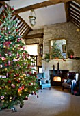 FULBROOK HOUSE: GALLERIED MAIN HALL WITH COTSWOLD STONE FIREPLACE  LOG BURNING STOVE  MIRROR AND LEATHER AND UPHOLSTERED ARMCHAIRS WITH CHRISTMAS TREE