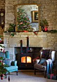 FULBROOK HOUSE: GALLERIED MAIN HALL WITH COTSWOLD STONE FIREPLACE  LOG BURNING STOVE  CHRISTMAS TREE REFLECTED IN MIRROR AND LEATHER AND UPHOLSTERED ARMCHAIRS