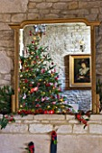 FULBROOK HOUSE: GALLERIED MAIN HALL GILT MIRROR ABOVE STONE FIREPLACE REFLECTING CHRISTMAS TREE