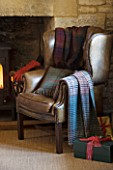 FULBROOK HOUSE: GALLERIED MAIN HALL WITH COTSWOLD STONE FIREPLACE AND LEATHER ARMCHAIR WITH CHRISTMAS PRESENTS
