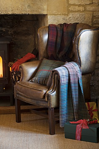 FULBROOK_HOUSE_GALLERIED_MAIN_HALL_WITH_COTSWOLD_STONE_FIREPLACE_AND_LEATHER_ARMCHAIR_WITH_CHRISTMAS