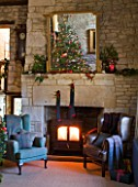 FULBROOK HOUSE: GALLERIED MAIN HALL WITH COTSWOLD STONE FIREPLACE  LOG BURNING STOVE AND LEATHER AND UPHOLSTERED ARMCHAIRS WITH CHRISTMAS TREE