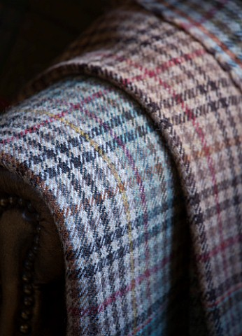 FULBROOK_HOUSE_SMALL_PLAID__WOOL_THROWS_BY_COTSWOLD_WOOLLEN_WEAVERS_ON_ARMCHAIR_BESIDE_FIRE_IN_HALLW